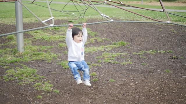 外遊び場で遊ぶスローモーション赤ちゃん女の子 - 余暇点の映像素材/bロール