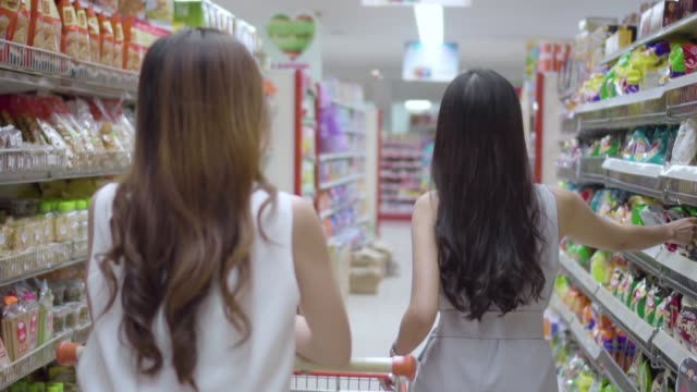slow motion : la vista posteriore di due donne che camminano fa shopping in un grande magazzino. - mar video stock e b–roll
