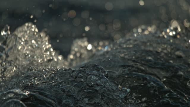 slow motion backlit river rapids water motion bubble splash - rapid stock videos & royalty-free footage