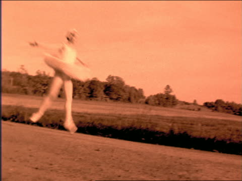 b/w orange slow motion pan ballerina in tutu leaping past camera outdoors - ballet dancer stock videos & royalty-free footage