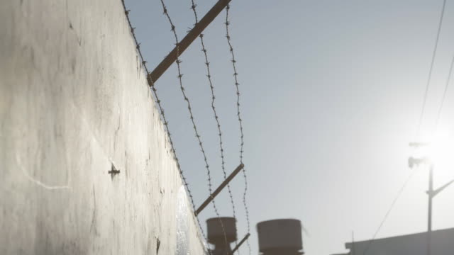 vidéos et rushes de slow motion, barbed wire wall with lens flare - prison