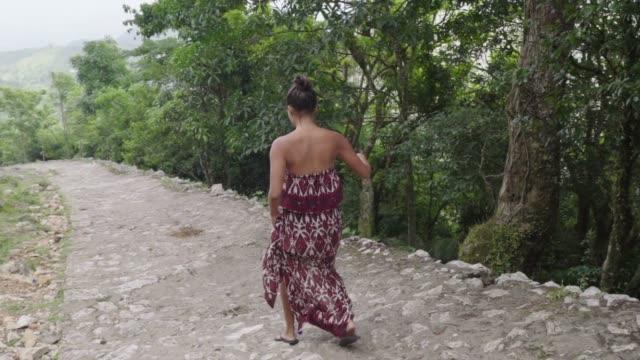 vídeos y material grabado en eventos de stock de slow motion: bare shouldered woman walks toward distant mountains - hispaniola