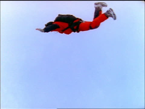 slow motion pan base jumper in red suit diving off cliff on snowy day / winter / europe - stunt person stock videos & royalty-free footage