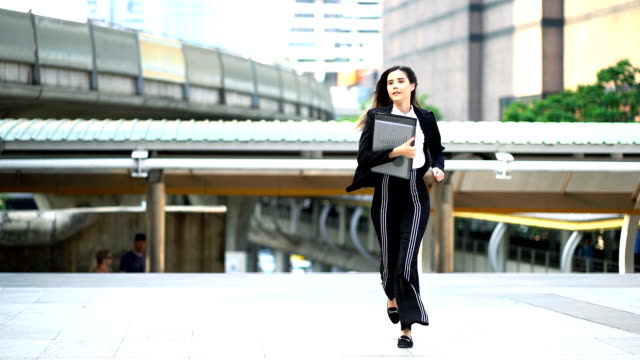 vídeos de stock e filmes b-roll de slow motion: beautiful business woman in black suit running up the staircase to work with modern office background - emprego e trabalho