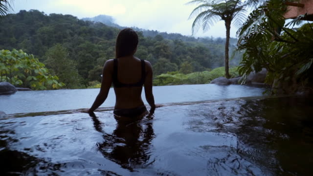 vídeos de stock e filmes b-roll de slow motion: beautiful woman in bikini watching the jungle from pool - costa rica