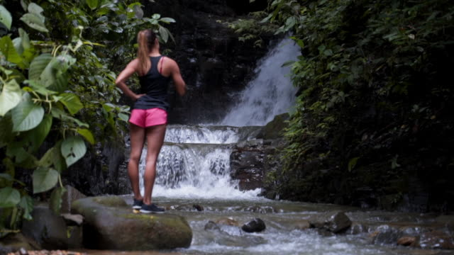slow motion: beautiful young woman at the bottom of scenic waterfall - tropical climate stock videos & royalty-free footage