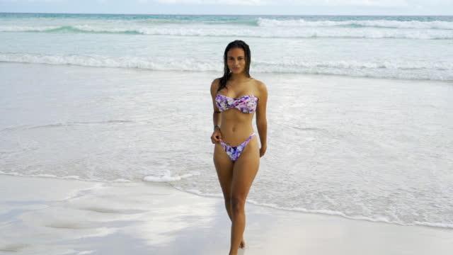 vidéos et rushes de slow motion: beautiful young woman in purple bikini walks out of gentle waves across beach toward camera  - galapagos islands, ecuador - maillot de bain