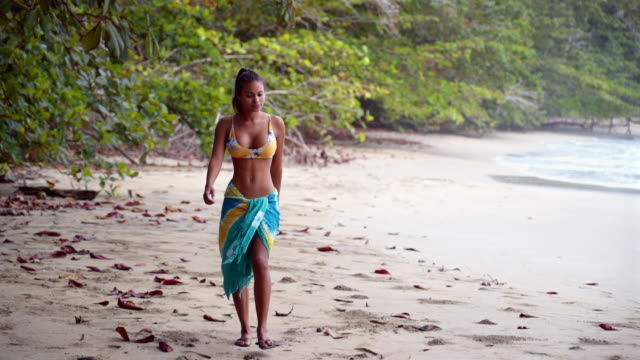 slow motion: beautiful young woman walking by the ocean next to the jungle - costa rica stock videos & royalty-free footage