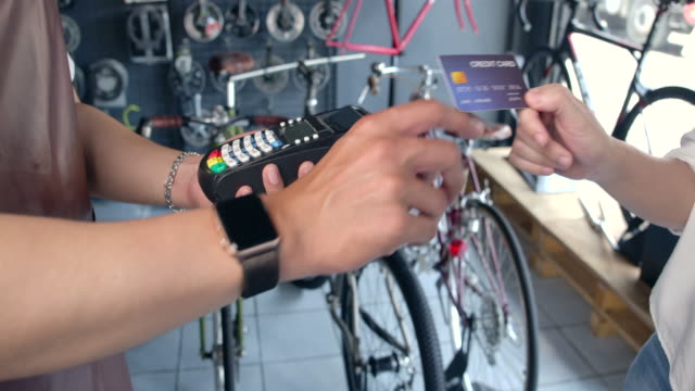 vídeos de stock e filmes b-roll de 4k slow motion bicycle shop owner this shop is a small business. that accept payment by credit card - vender