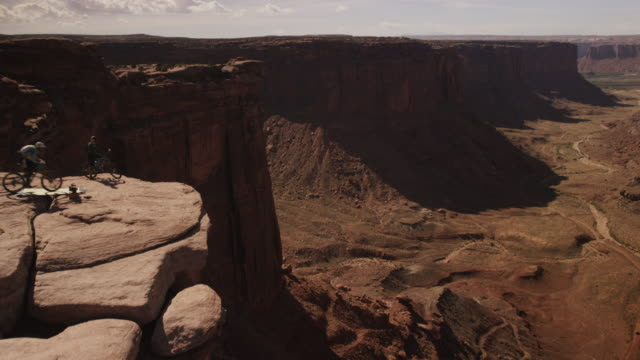 slow motion, biker jumps off cliff with parachute - moab utah stock videos and b-roll footage