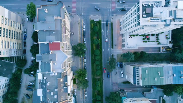 slow motion bird's eye looking down shot of a drone flying over city - on top of stock videos & royalty-free footage