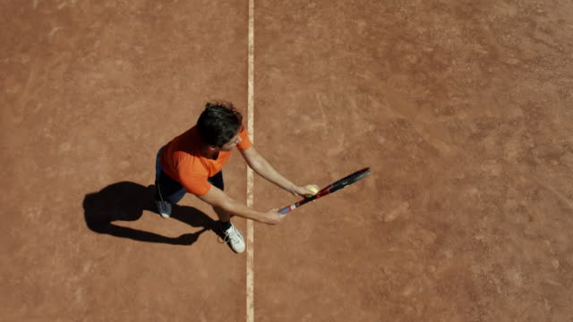 vídeos de stock e filmes b-roll de slow motion birds eye view of man on clay tennis court serving and setting up to return - ténis calçado desportivo