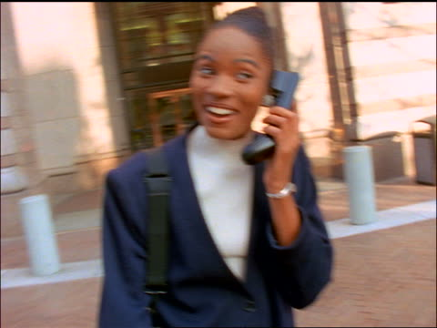 vidéos et rushes de slow motion black businesswoman laughing while talking on cellular phone in front of office building - historique