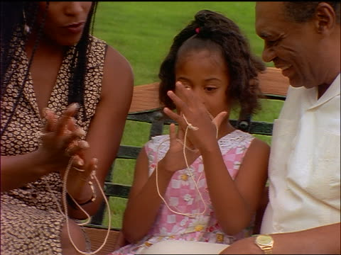 slow motion black girl playing cat's cradle with mother + grandfather on bench outdoors - cat's cradle stock videos & royalty-free footage