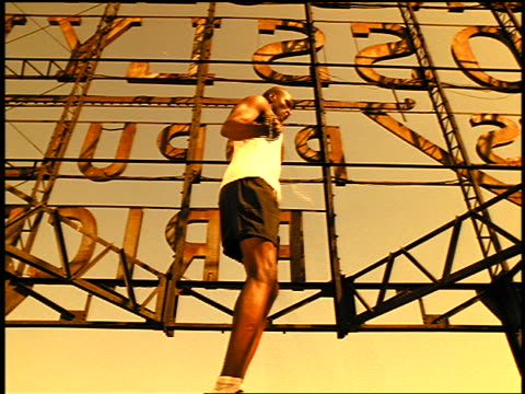 sepia slow motion black male athlete jumping rope on rooftop below large sign - getönt stock-videos und b-roll-filmmaterial