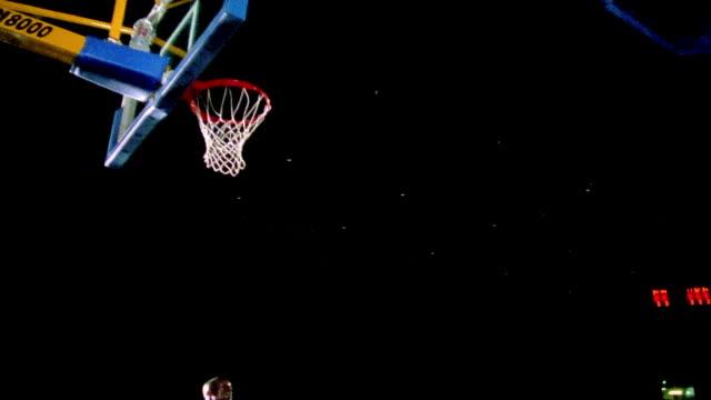 vídeos y material grabado en eventos de stock de slow motion black man in uniform doing reverse dunk in basketball hoop / black background - canasta de baloncesto