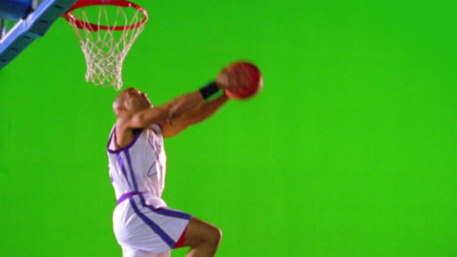 vídeos y material grabado en eventos de stock de slow motion ms black man in uniform dunking basketball + hanging on rim of hoop in front of green screen - mate imagen en movimiento