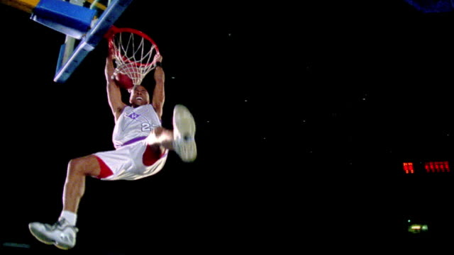 slow motion Black man in uniform dunking basketball hanging on rim of hoop / zoom in giving attitude to camera