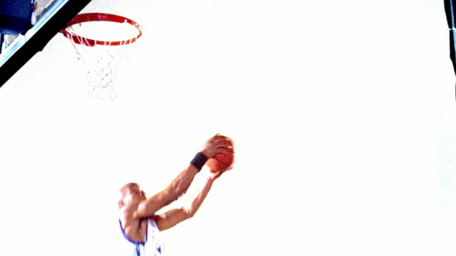 vidéos et rushes de overexposed slow motion black man in uniform dunking basketball + hanging on rim of hoop / white background - panier