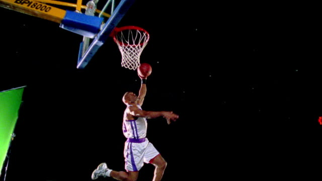 slow motion Black man in uniform dunking basketball / posing with attitude + talking to camera / black background