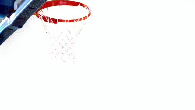 vidéos et rushes de overexposed slow motion ms black man in uniform dunking basketball / white background - fond blanc