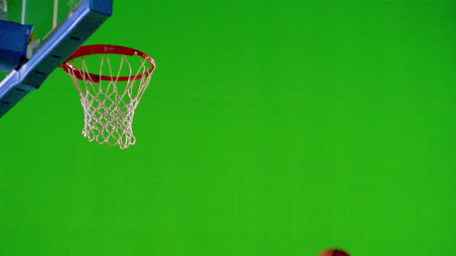 slow motion black man in uniform spinning + dunking basketball in front of green screen - shooting baskets stock videos and b-roll footage