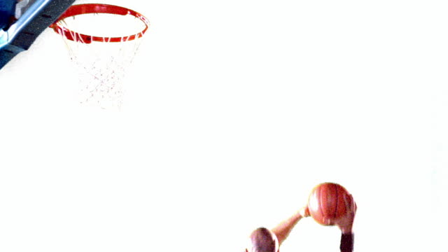 overexposed slow motion ms black man in uniform spinning + dunking basketball / white background - overexposed stock videos & royalty-free footage