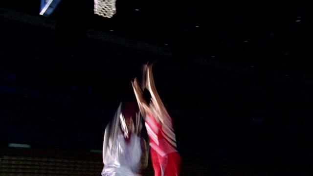 slow motion SWISH PAN Black man in white uniform dunking basketball as man in red tries to block