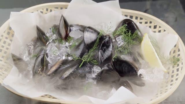 fhd slow motion : schwarze muscheln auf schwarzer steinplatte mit zitrone und dill mit fluss von gefrorenem eisigem rauch. frische luxus meeresfrüchte und menü rezepte einzelhandel marktkonzept. - schalentier stock-videos und b-roll-filmmaterial