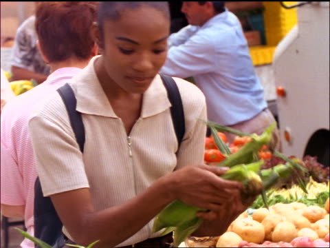 slow motion Black woman choosing corn at produce stand at outdoor market
