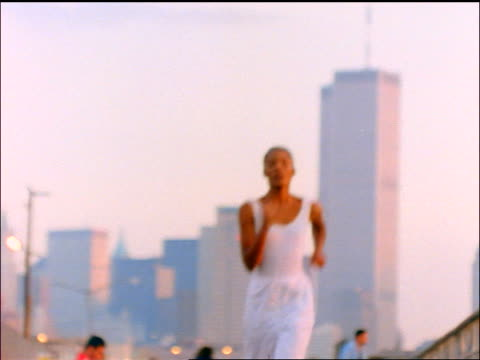 slow motion Black woman in white jogging towards camera / World Trade Center in background / NYC