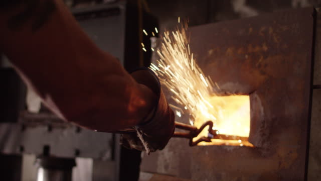 slow motion, blacksmith moves rod in forge - blacksmith stock videos & royalty-free footage