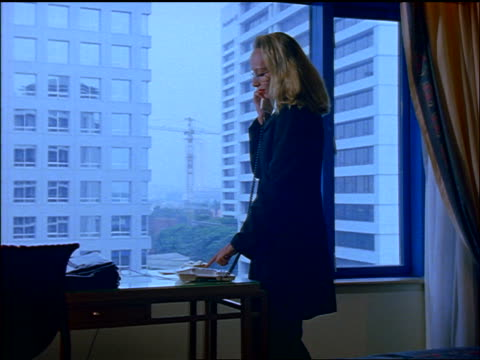 slow motion blonde businesswoman standing by window + dialing telephone in hotel room / jakarta - 加入電話点の映像素材/bロール