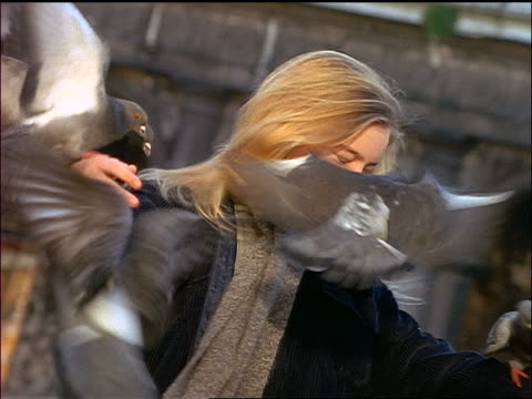 slow motion blonde girl covered by pigeons spinning around - endast flickor bildbanksvideor och videomaterial från bakom kulisserna