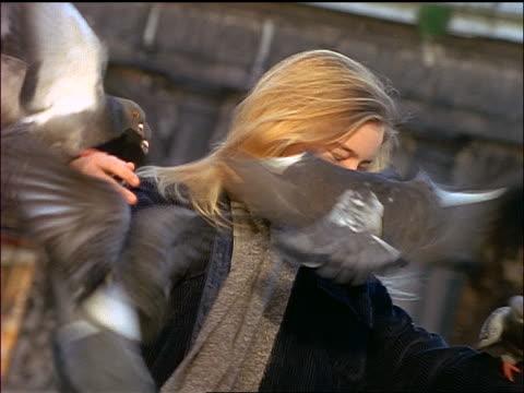 stockvideo's en b-roll-footage met slow motion blonde girl covered by pigeons spinning around - alleen meisjes