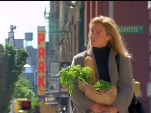 slow motion blonde woman carrying groceries walking on downtown nyc street towards camera - 1990~1999年点の映像素材/bロール