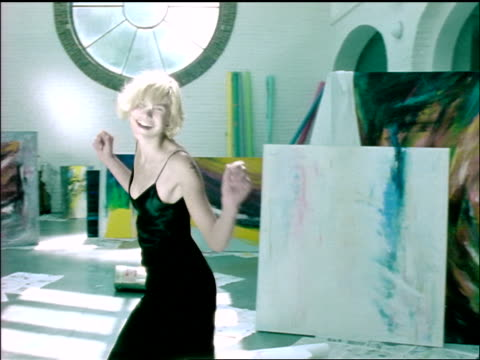 vidéos et rushes de slow motion blonde woman dancing + smiling for camera around paintings in large studio - 1990 1999