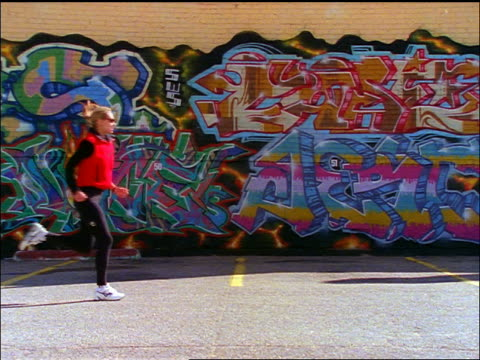 stockvideo's en b-roll-footage met slow motion blonde woman running past graffiti-covered wall - jogster