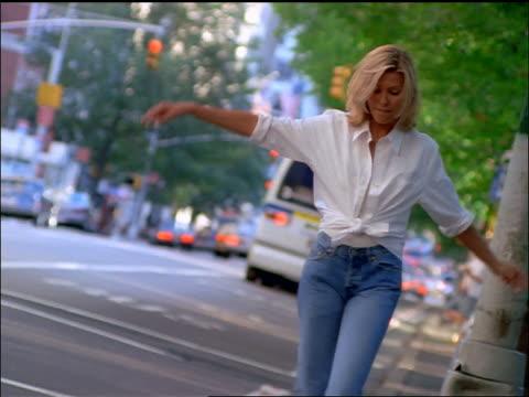 slow motion blonde woman walking on edge of curb on nyc street - 1990~1999年点の映像素材/bロール
