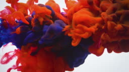 Slow motion blue and red ink flow in water.