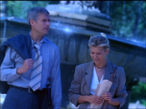 vídeos de stock e filmes b-roll de slow motion blue canted business couple walking in front of fountain + talking / nyc - fonte bethesda
