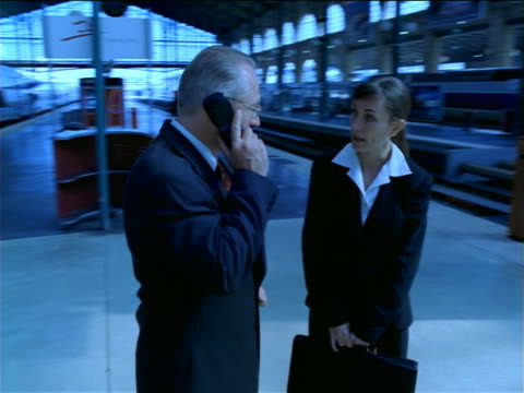 slow motion BLUE dolly shot around, toward + away from businessman + woman talking/man on cell phone/Gare de Lyon