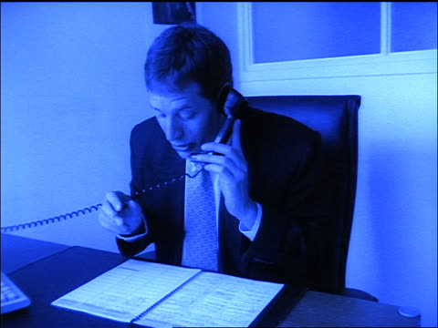 stockvideo's en b-roll-footage met slow motion blue dolly shot zoom in businessman on phone at desk writing in appointment book - mid volwassen mannen