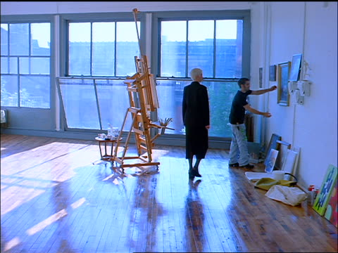 slow motion BLUE Gen X man in loft handing woman in black painting on wall