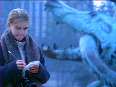 slow motion blue rack focus blonde girl standing in park sketching statue of alligator eating serpent - solo adolescenti femmine video stock e b–roll