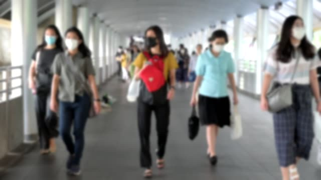 slow motion blur focused. the crowd is wearing protective masks prevent coronavirus, covid 19 virus during virus outbreak and pm2.5 air pollution crisis rush hour bangkok, thailand. - schutz und arbeitskleidung stock-videos und b-roll-filmmaterial