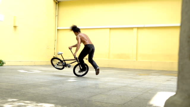 slow motion bmx flatland spin trick , asian model. - balance stock videos and b-roll footage