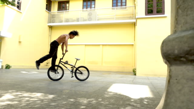 slow motion bmx flatland spin trick , asian model. - bmx cycling stock videos and b-roll footage