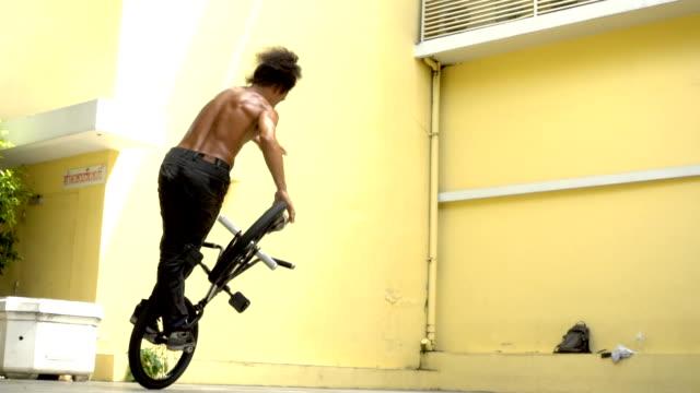 vídeos de stock, filmes e b-roll de truque de rotação lenta bmx flatland, modelo asiático. - proeza acrobática