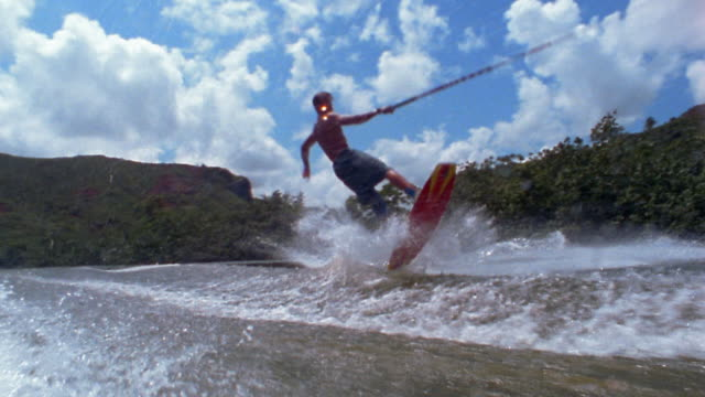 slow motion boat point of view man riding wakeboard, flipping in air and landing on water / kauai, hawaii - wakeboarding stock videos and b-roll footage